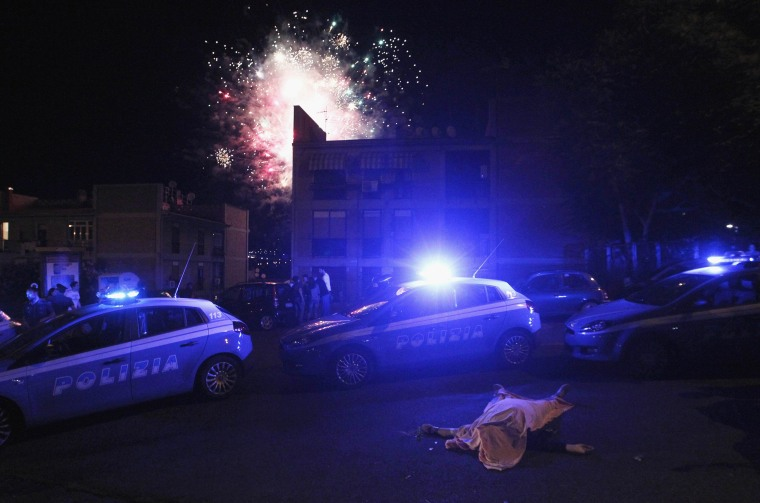 Image: Police patrol area around man killed after shooting, as fireworks are set off at local party in background, in Naples