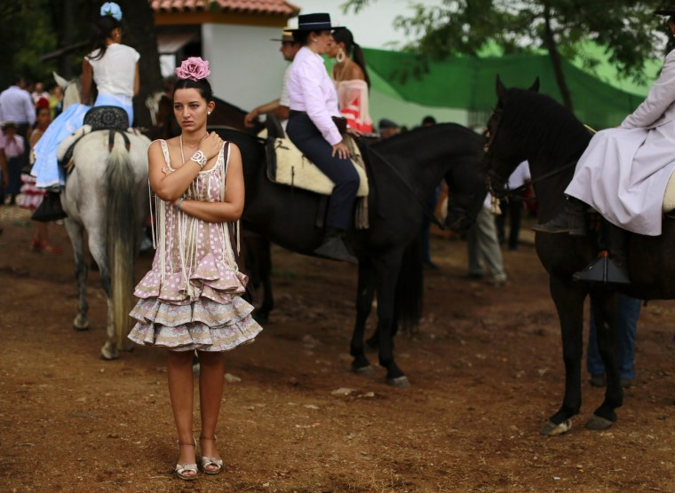 Image: A pilgrim wearing a flamenco outfit stands during a pilgrimage in Alajar, southwest Spain