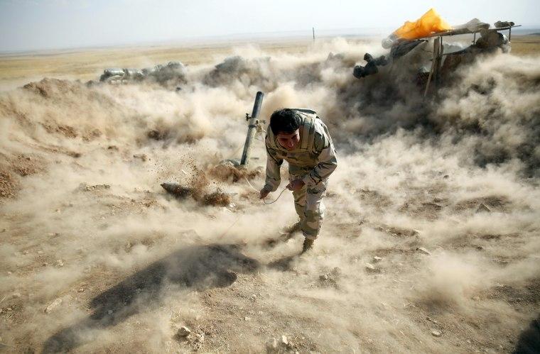 Image: A Kurdish Peshmerga fighter launches mortar shells towards Zummar, controlled by Islamic State, near Mosul