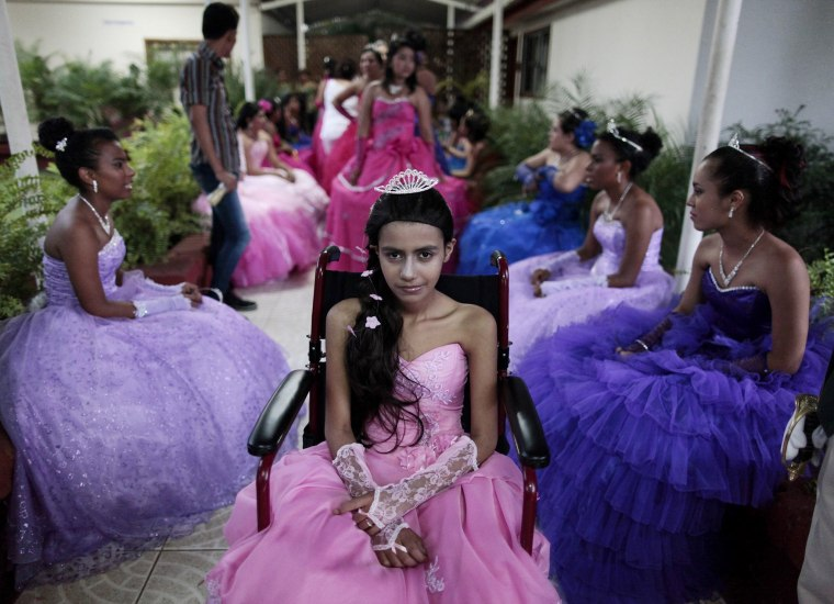 """Image: A cancer patient poses for a photo during her """"Quinceanera"""" (15th birthday) party among other celebrants at a hotel in Managua"""