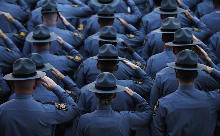 Image: Pennsylvania State Police salute as they line the streets outside St. Peters' Cathedral in Scranton, as the casket carrying slain Pennsylvania State Police Trooper Corporal Bryon Dickson is carried into the Cathedral for his funeral service