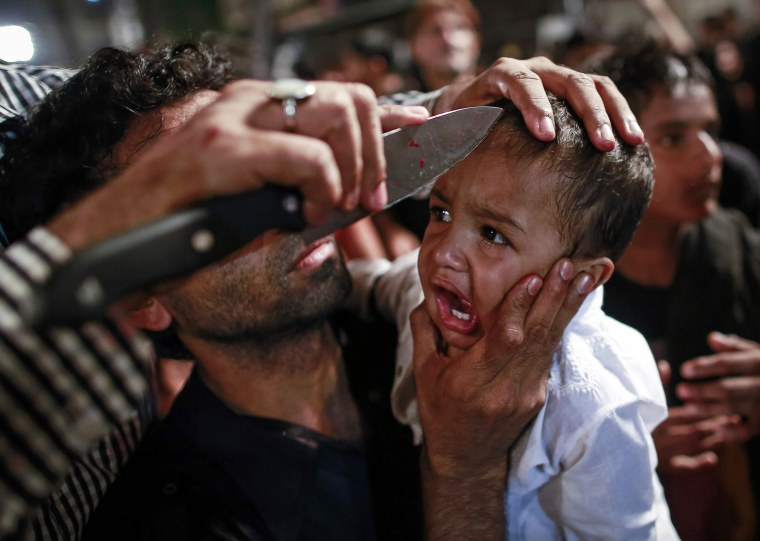Image: A Shi'ite Muslim has his child gashed with a knife during a Muharram procession ahead of Ashoura in Mumbai