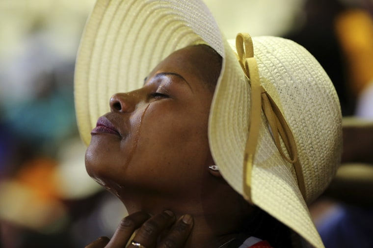 Image: A woman reacts during a joint memorial service for South African athletes, Meyiwa, Mwelase and Mulaudzi, in Johannesburg