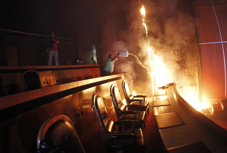 Image: A man tries to extinguish a fire set alight at the principal hall of the City Congress by CETEG members, in Chilpancingo