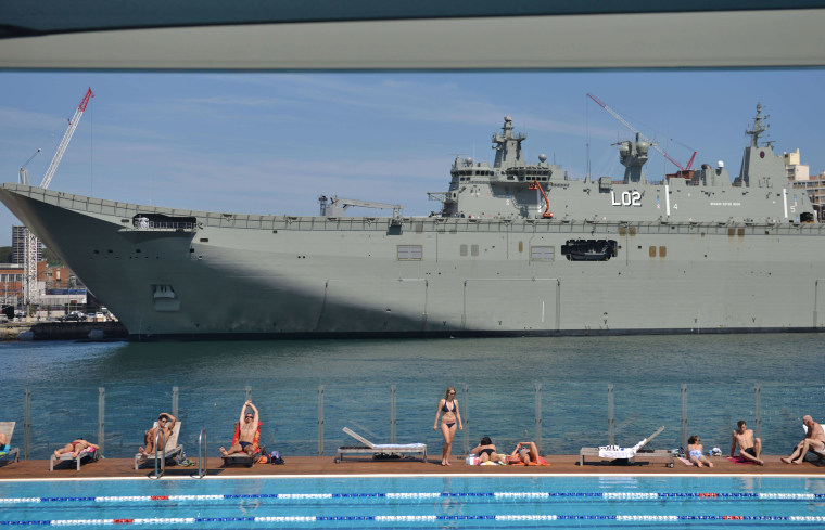 Image:  People sunbathe at a swimming pool in front of HMAS Canberra