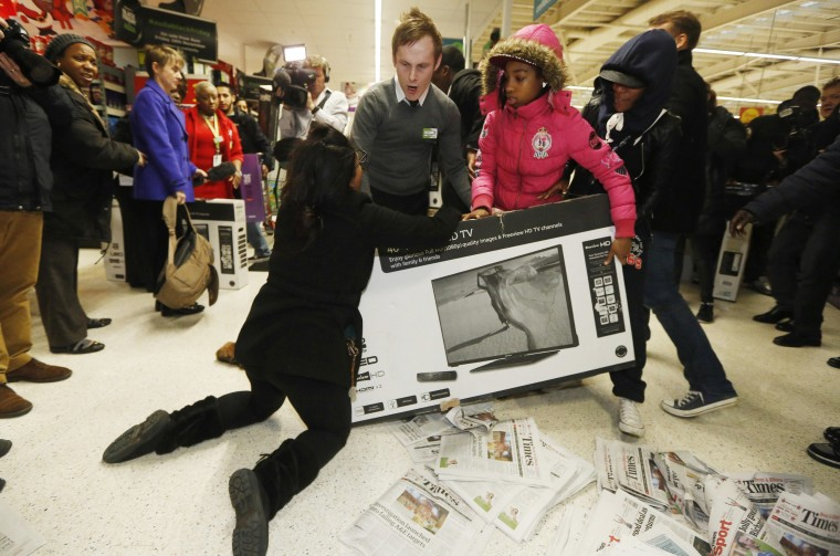 """Image: Shoppers wrestle over a television as they compete to purchase retail items on """"Black Friday"""" at an Asda superstore in Wembley"""