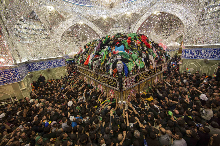 Image: Shi'ite Muslim pilgrims reach out to touch the tomb of Imam al-Abbas located inside the Imam al-Abbas shrine to mark Arbain in the holy city of Kerbala