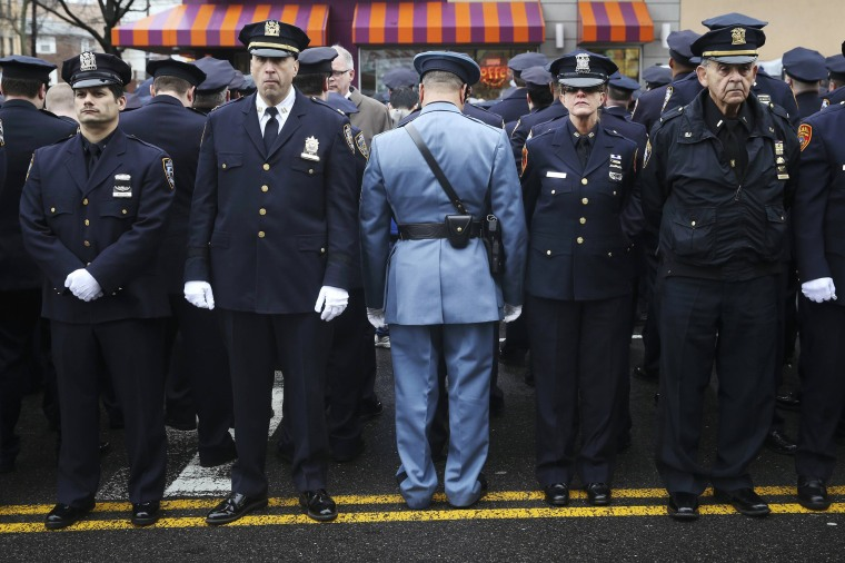 Image: Law enforcement officers stand, with some turning their backs, as New York City Mayor Bill de Blasio speaks on a monitor outside the funeral for NYPD officer Wenjian Liu in the Brooklyn borough of New York