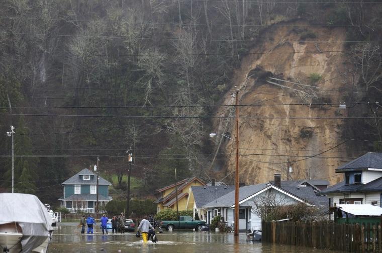 Image: People walk along a flooded street near a landslide
