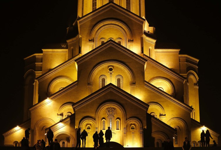 Image: People walk in front of the Holy Trinity Cathedral during midnight Christmas service in Tbilisi
