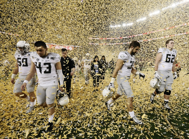 Image: Oregon players walk off the field after the NCAA college football playoff championship