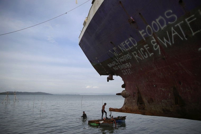 Image: Divers take a part in an effort to recover a ship brought inland by Typhoon Haiyan in Tacloban