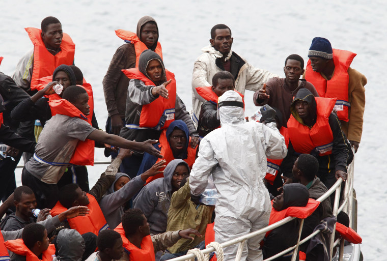 Image: Rescued migrants on the deck of an Armed Forces of Malta (AFM) patrol boat reach out for bottles of water being distributed by a soldier in a biohazard suit after arriving at the AFM's Maritime Squadron base at Haywharf in Valletta's Marsamxett Har