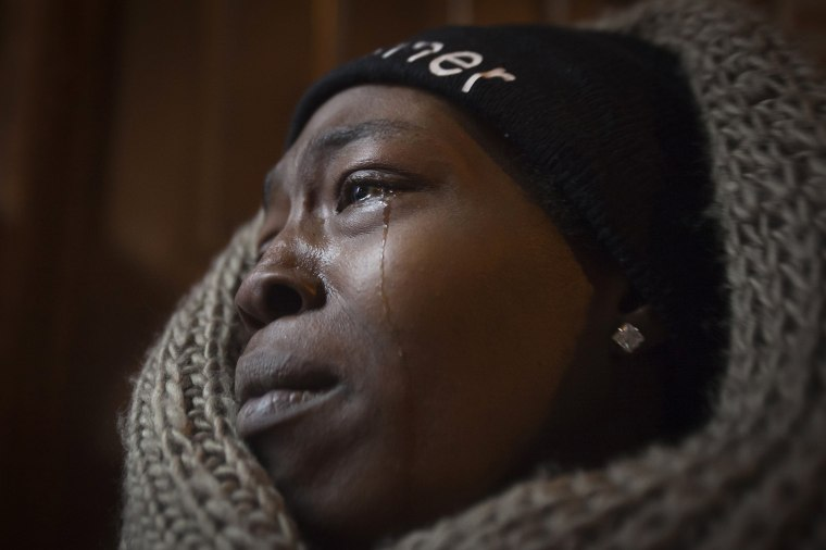 Image: Tears stream down the face of a woman during a candlelight vigil at the site where Garner died after being put in a chokehold, during a Martin Luther King Day service in New York