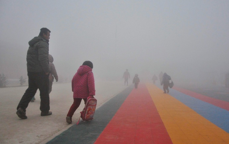 Image: Parents walk primary school students to school amid thick haze in Chiping county
