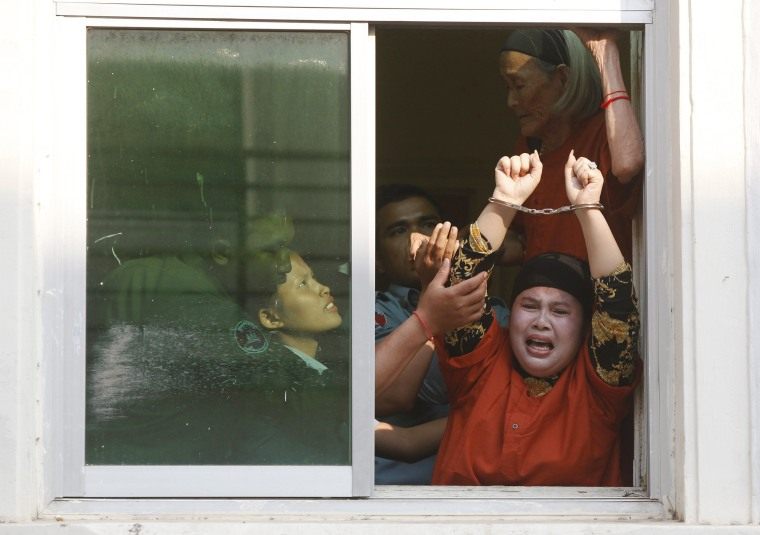 Image: Housing rights defenders shout from window as they arrive to the appeals court in Phnom Penh