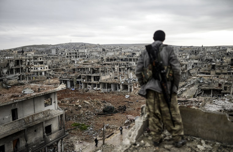 Image: Musa, a 25-year-old Kurdish marksman, stands atop a building