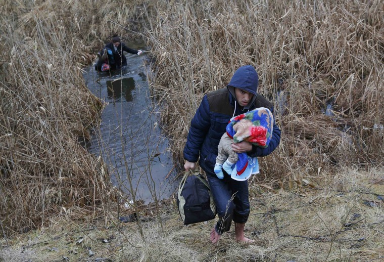 Image: A Kosovo man carries his baby as he crosses illegally the Hungarian-Serbian border near the village of Asotthalom