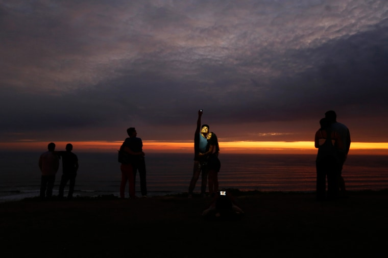 Image: Couple takes a selfie as others observe the sunset at an oceanfront in the neighbourhood of Miraflores in Lima