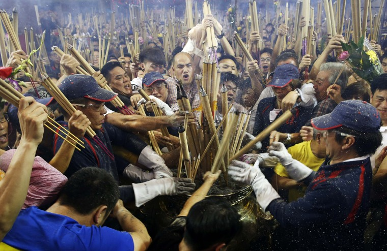 Image: People rush to plant the first joss stick of the Lunar New Year at the stroke of midnight at the Kwan Im Thong Hood Cho temple in Singapore
