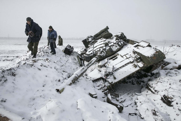 Image: Members of the separatist self-proclaimed Donetsk People's Republic army collect parts of a destroyed Ukrainian army tank in the town of Vuhlehirsk, west of Debaltseve