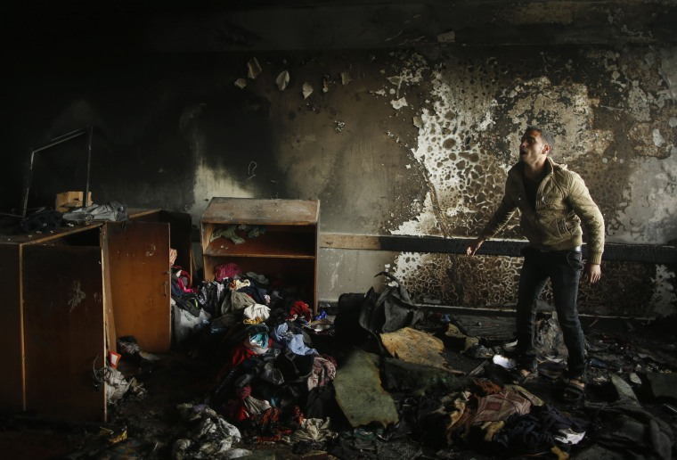 Image: A Palestinian man reacts as he inspects a burnt classroom at a UN-run school sheltering Palestinians in Biet Hanoun