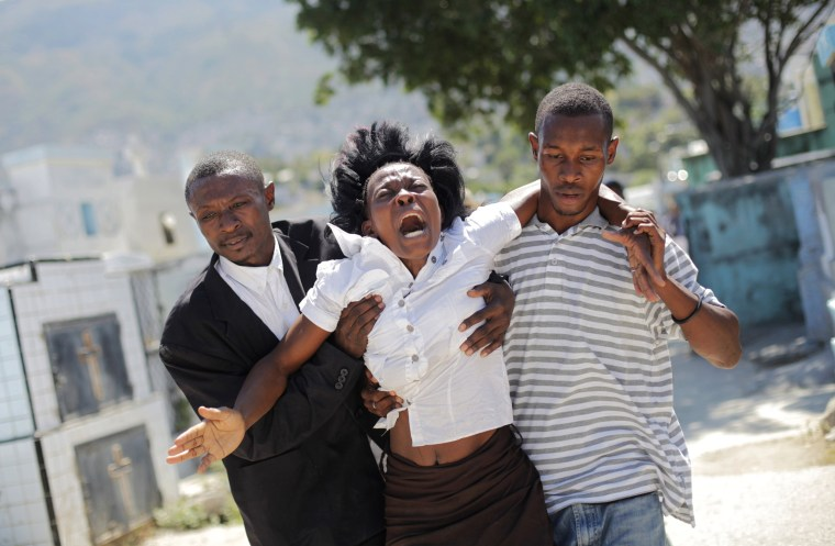 Image: A woman reacts as others help her walk at the cemetery before the funeral for the victims of a Carnival stampede, in Port-au-Prince