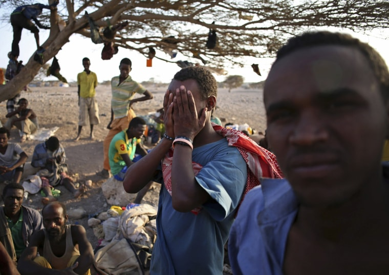 Image: An illegal immigrant from Ethiopia covers his face as he waits with others for a boat to cross into Yemen outside the town of Obock, north Djibouti