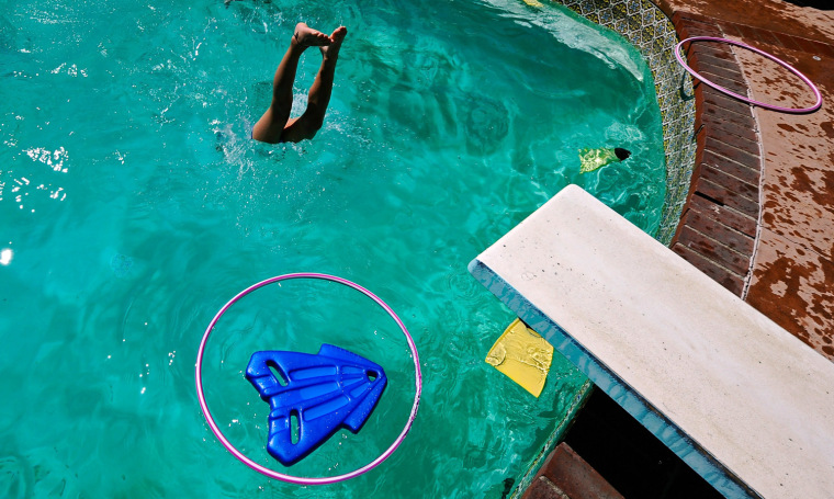 Image: A child plays in a backyard pool in Los Angeles, California