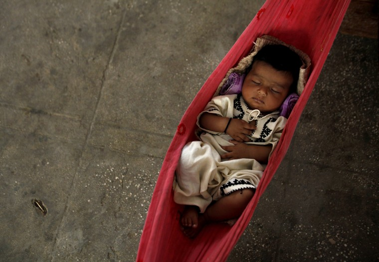 Image: Three-month-old Nasiba sleeps in a hammock while taking refuge from the flood with her family in a classroom in Sukkur, Pakistan