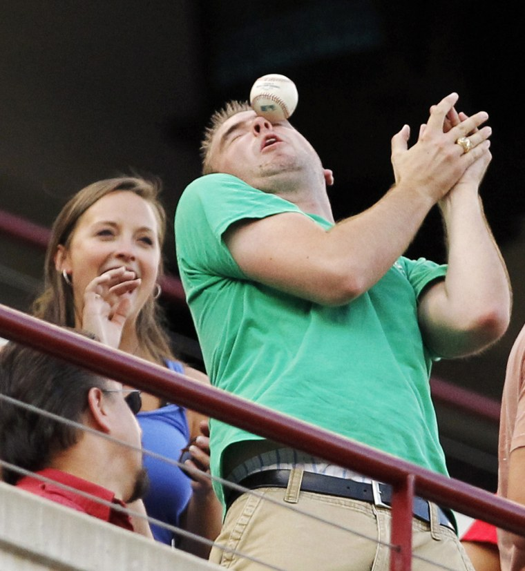 Image: An unidentified fan is struck by a foul ball during the baseball between Minnesota Twins and Texas Rangers