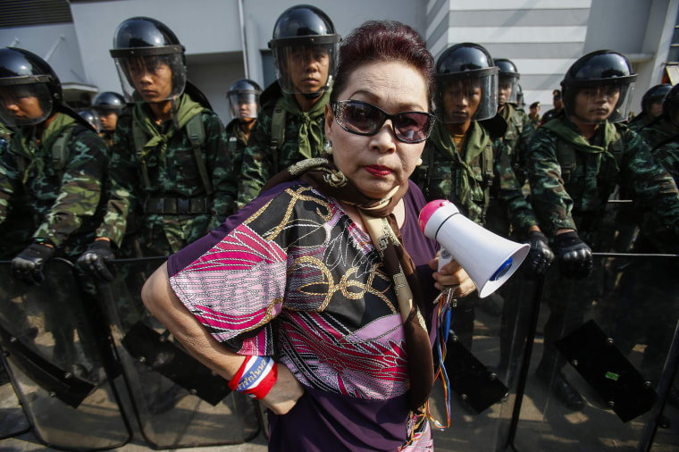Image: An anti-government protester stands near Thai soldiers guarding a Defence Ministry compound in north Bangkok