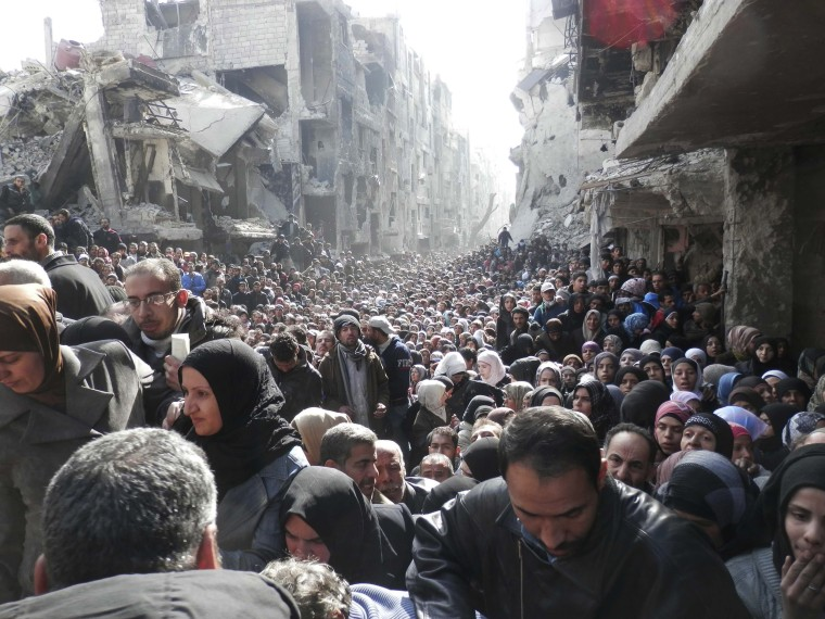 Image: Residents wait to receive food aid distributed by the U.N. Relief and Works Agency (UNRWA) at the besieged al-Yarmouk camp, south of Damascus