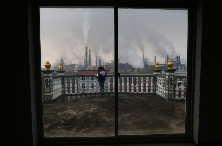Image: A girl reads a book on her balcony as smoke rises from chimneys of a steel plant, on a hazy day in Quzhou