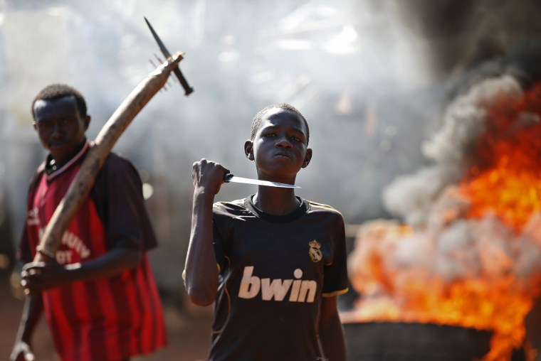 Image: A boy gestures in front of a barricade on fire during a protest after French troops opened fire at protesters blocking a road in Bambari