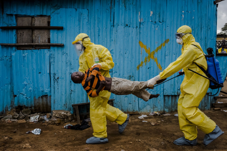 Image: Medical staff carry James Dorbor, 8, suspected of having Ebola, into a treatment facility in Monrovia, Liberia.