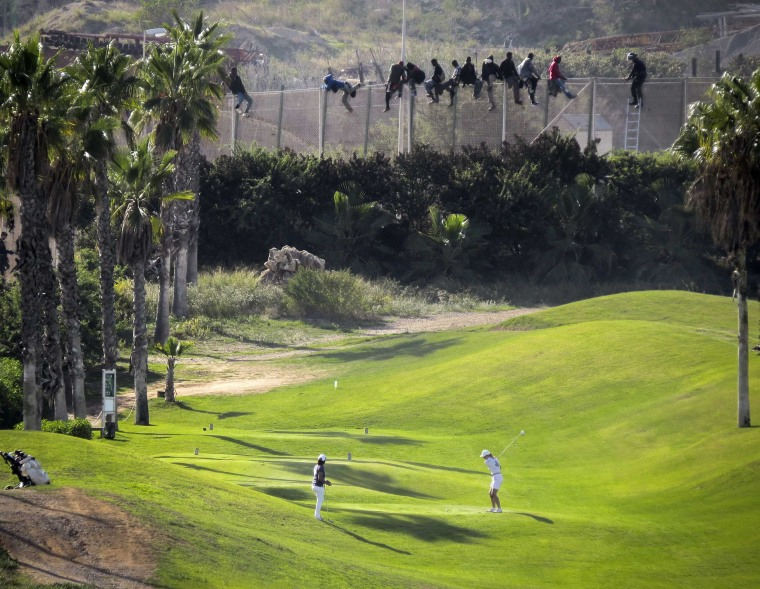 Image: A golfer hits a tee shot as African migrants sit atop a border fence during an attempt to cross into Spanish territories between Morocco and Spain's north African enclave of Melilla
