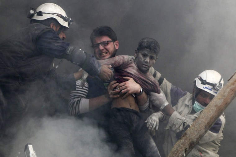 Image: Men rescue a boy from under the rubble after what activists said was explosive barrels dropped by forces loyal to Syria's President Bashar Al-Assad in Al-Shaar neighbourhood of Aleppo