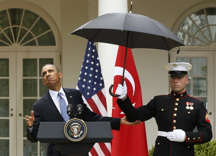 Image: U.S. President Obama checks the need for and umbrella held by a U.S. Marine during a joint news conference with Turkish Prime Minister Erdogan in Washington