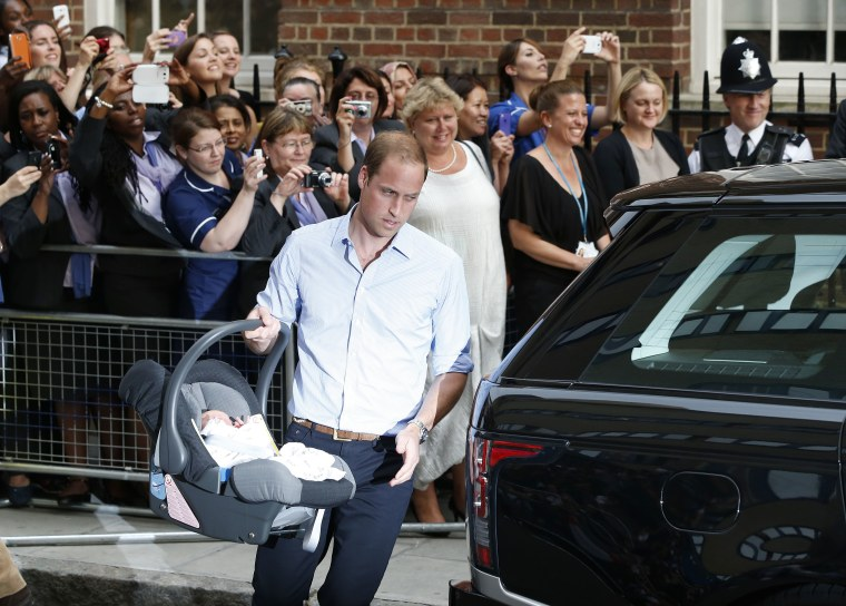 Image: Britain's Prince William carries his son the Prince of Cambridge into a car outside St. Mary's Hospital.