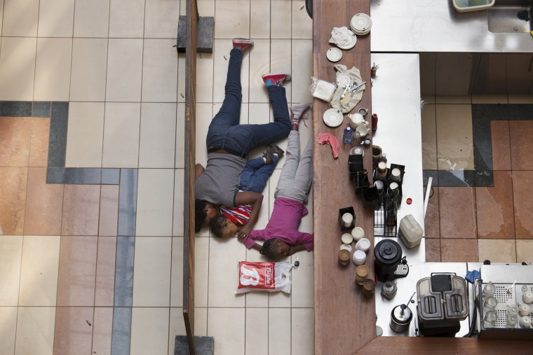Image: A woman and children hide inside Westgate Mall in Nairobi, Kenya, Sept. 21, 2013.