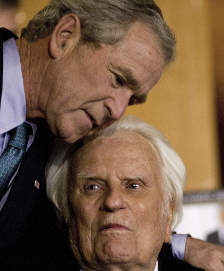 Image: Former U.S. President George W. Bush shares a hug with Billy Graham while signing copies of his new book in Charlotte