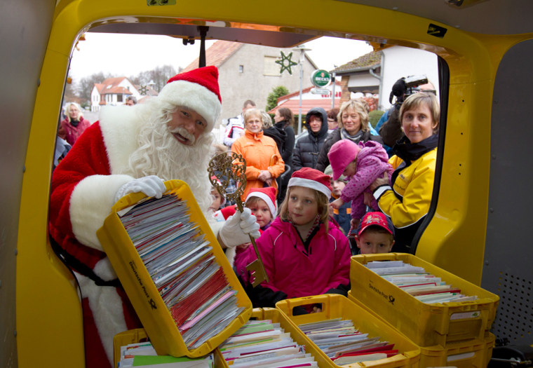 Image: A man dressed as Father Christmas carries crates with letters addressed to Santa Claus at special Christmas post office in village of Himmelpfort