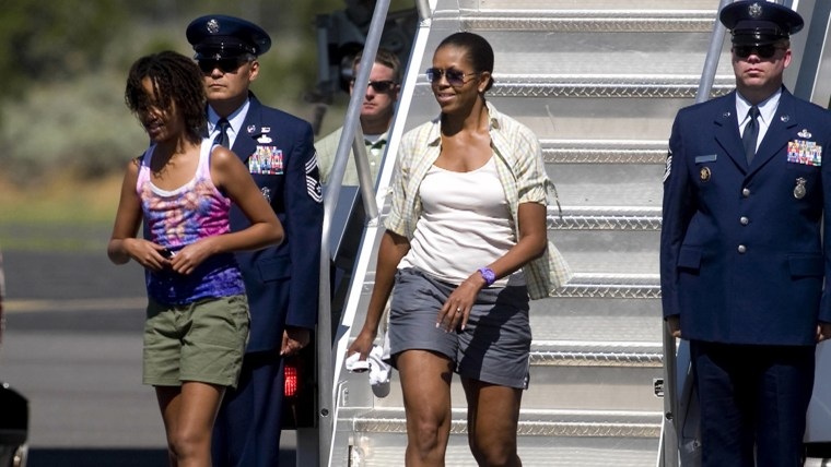 Image: Michelle Obama departs an airplane wearing gray shorts.