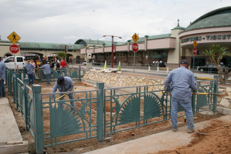 Workers clean up the pet-relief area outside El Paso International Airport.