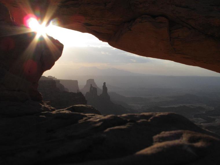 The morning sun just peeking through Mesa Arch in Canyonlands National Park, Utah.