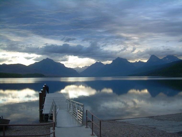Man enjoying the early morning view of Lake MacDonald in Glacier National Park, Montana.