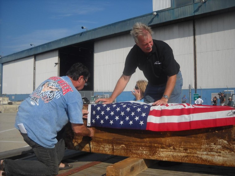 Men secure a flag overa World Trade Center beam prior to transportation to Erie, Pa., for construction of a memorial to remember the events of Sept. 11, 2001.