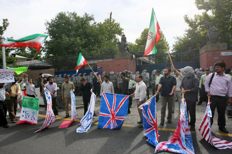 Supporters of Iran's government protest outside the British Embassy in Tehran on Tuesday,later burning the British, U.S. and Israeli flags.
