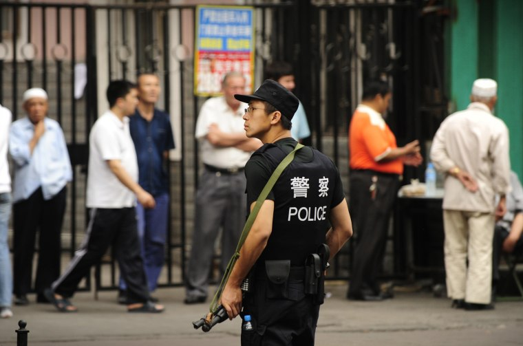 """A Chinese policeman keeps watch Mondayon a street in Urumqiwhere police said they shot dead two Muslim Uighur """"lawbreakers"""" earlier in the day."""